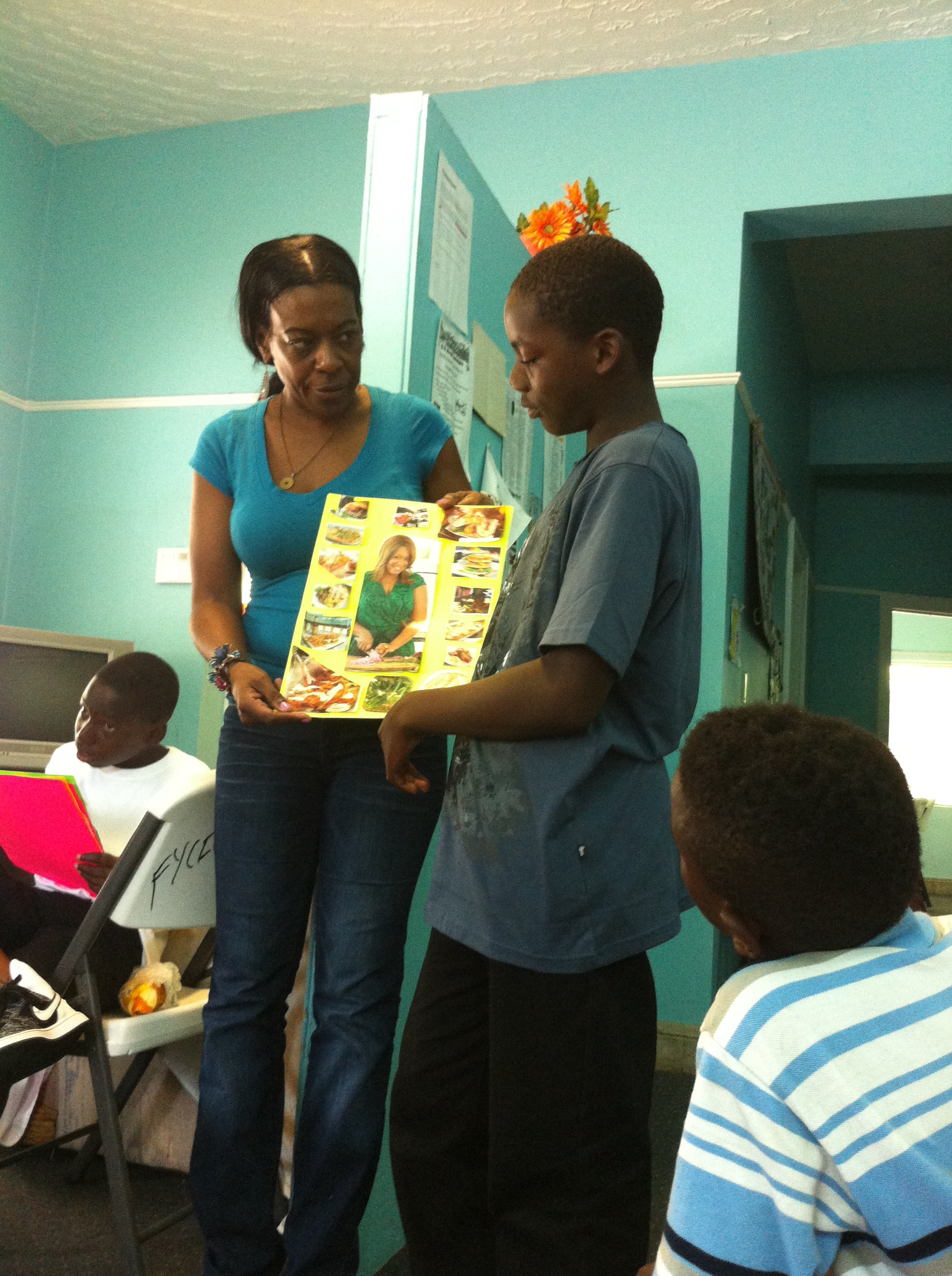 Teaching self pride and respect through cultural literacy, Dr. Celia Victor helps a student present his vision board to the parents, facilitators and other youth.